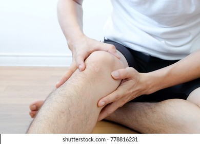 young man sit with knee pain and feeling bad hand on her knee  at room,  Health care concepts