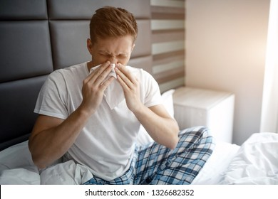 Young man sit on bed early morning. He sneeze into white napkin. Sick and ill young man.