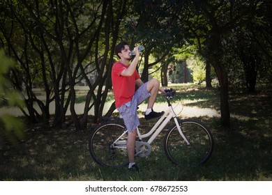 young man sit on bike in wood resting drink water  summer day real people concept
