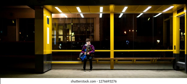 young man sit on the bus stop bench waiting in the night