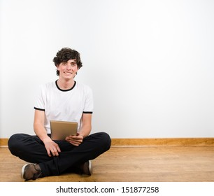 Young man sit on floor with a laptop smiling