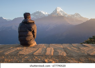 A young man sit on the floor is looking to the high mountains in the Himalaya, Nepal