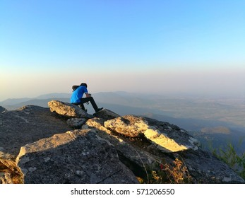 young man sit on the stone and enjoyed with mountain view.