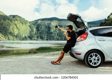 Young man sits in the car trunk take selfie photo on phone near beauty lake background. Summer vocation