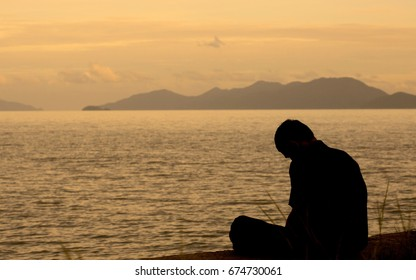 The young man sits face down, desperate and alone, feeling like something is decided on the beach with the light from the sunset.
