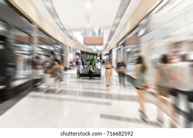 Young man sits motionlessly inside modern mall. People fast moves past him by motion blur style. Concept of consumer society and fast paced life