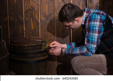 Young man sits near a barrel and trying to solve a conundrum to get out of the trap, escape the room game concept
