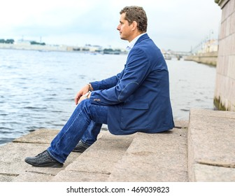 young man sits near the water