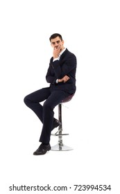 A young man sits on a bar high chair, a business suit, a serious look, is inexhaustible or a financier, or an office employee. Isolate on white background. He thinks and rubs his chin.