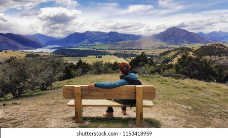 A young man sits on a bench on the summit of a hill on the background of the Wanaka Mountains in New Zealand.