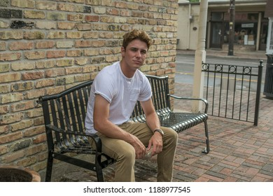 Young man sits on a bench in a retro area of town wearing a white shirt and khaki pants on a nice sunny day.