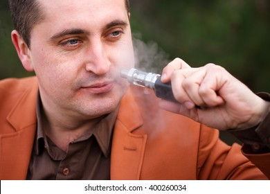 A young man sits on a bench and smokes an electronic cigarette.