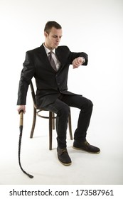 young man sits on a chair and looks at the clock with whip in hand  on white background