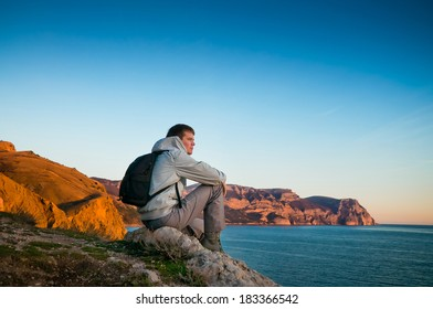 A young man sits on a hill and enjoys sea sunset