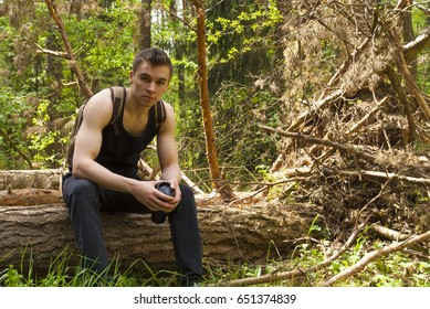 A young man sits on a log on a Sunny summer day
