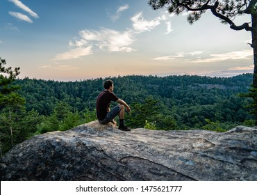 A young man sits on an outcropping of rock atop a mountain in Red River Gorge, Daniel Boone National Forest, Kentucky.