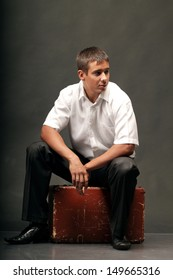 A young man sits on a suitcase.