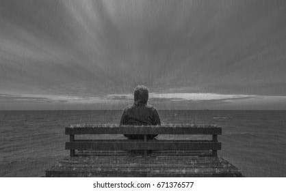 The young man sits on a wooden chair in the sea in the rain. He freed up the mood he did not want to disappear with rain.