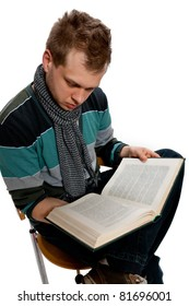 A young man sits reading book in the studio posing on a white background