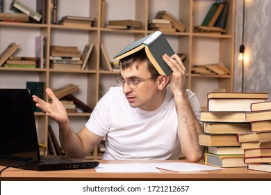 a young man sits at a table with books and looks into a laptop with his head covered in a book. difficulties online work. distance learning. bookcase on the background. emotions.