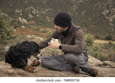 Young man sits at the top of the mountain with his dog and a cup of hot drink in his hands. On a cloudy and cold autumn day.