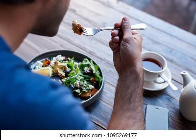 Young man sitting alone at a bistro table eating a delicious plate of mixed salad and drinking a cup of tea