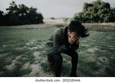 Young man sitting alone in a field of grass desperately thinking with his face in his hands