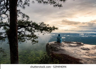 Young Man sitting alone in forest outdoor with sunset nature on background Travel Lifestyle and survival concept