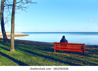 The young man sitting alone on a bench against the sea.
