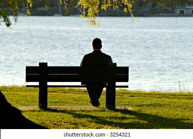 Young man sitting alone on park bench under a willow tree, looking down to the water.