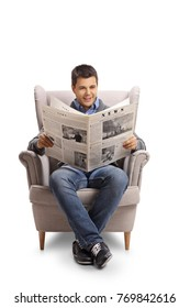 Young man sitting in an armchair and reading a newspaper isolated on white background