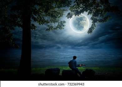 Young man sitting back playing guitar on a beautiful full moon night.