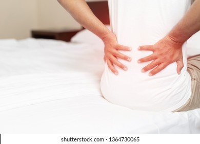 Young Man Sitting in bedroom suffering from back pain in the morning. after sleeping on bad mattress in incorrect posture, suffering from painful periods concept. color red emphasize Lower back ache.