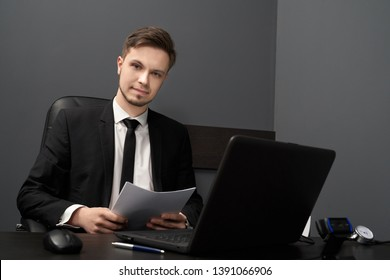 Young man sitting at black table with computer polygraph in grey room. Handsome man with beard in black suit holding paper, looking at camera. Concept of lie detector.