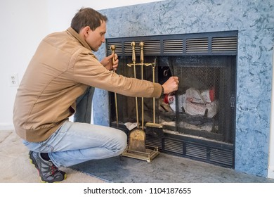 Young man sitting by indoor home interior fireplace with screen mesh, old retro vintage golden gold instruments tools, or accessories such as dusty shovel, poker, tongs and broom