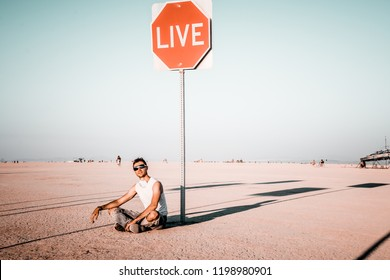 Young man sitting by the live sign in the middle of a desert at the Burning Man festival. Sign to live your life.