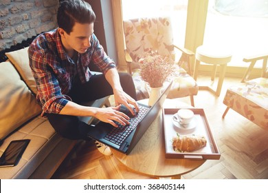 Young man sitting at a cafe, using a laptop