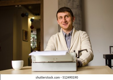 Young man sitting in cafe and work on the typewriter