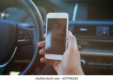 Young man sitting in the car and writes a message on the phone