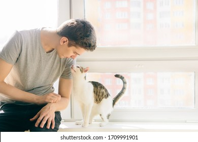 young man is sitting with a cat on the windowsill. Favorite pet. Man with a cat on a background of a window with sunlight