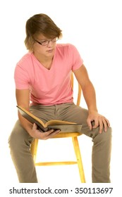 a young man sitting in a chair, holding a book and thinking.
