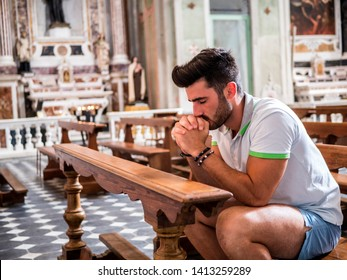 Young man sitting in church praying, with his hands joined together