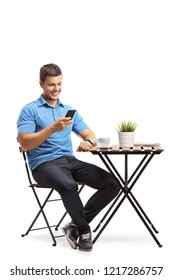 Young man sitting at a coffee table and using a mobile phone isolated on white background
