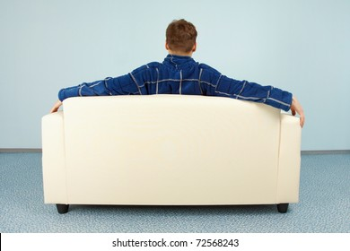 A young man is sitting comfortably at home on the couch