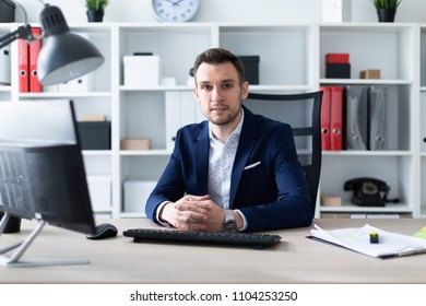 A young man is sitting at the computer desk in the office.