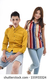young man sitting cube and woman posing in studio