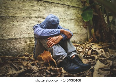 A young man sitting in a dark corner is a psychotic stress, depression, anxiety, needing help.