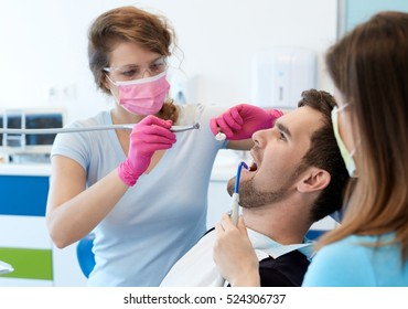 Young man sitting in dentist's chair, having dental treatment.