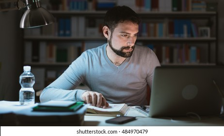 Young man sitting at desk, using a laptop, working late at night, he is studying a book and using a laptop