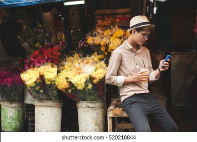 Young man sitting at flower counter and text messaging
